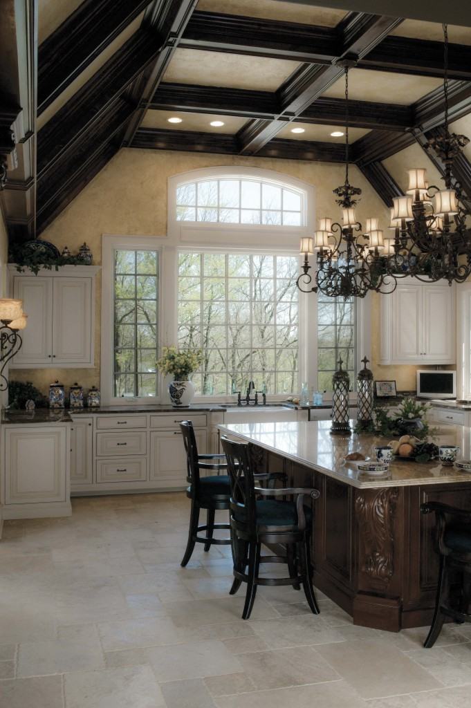 Dark beams, high ceilings and a mixture of wood tones with white cabinetry complement this kitchen design